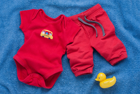 ducky: Single red baby pants and bodysuit decorated with school bus patch next to yellow rubber ducky over plush blue towel background