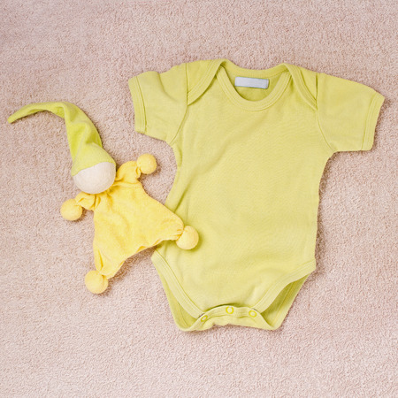 carpeting: Yellow newborn button up onesie and toy clown with night hat on top of soft pink carpeting
