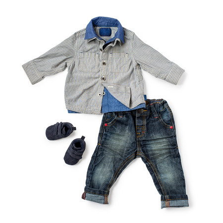 velcro: Child size button shirt, rolled up jeans and pair of matching velcro shoes over white background