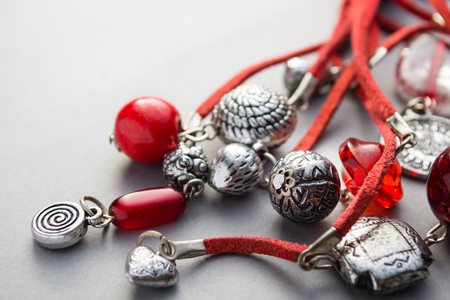 charms: Close up of red glass beads and silver charms attached to leather string on gray background Stock Photo