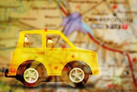 small world: Yellow childrens car before sending on a journey through the geographical map Stock Photo
