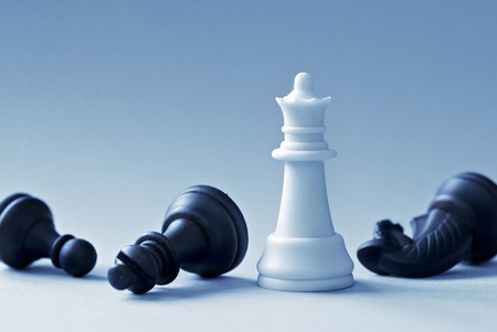 White Chess Queen and defeated black shapes on a light blue background Banque d'images