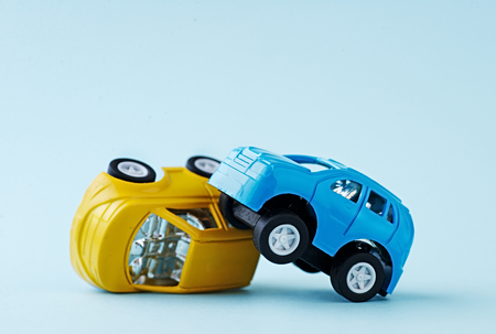 Close-up of two toy cars accident on a blue background Stock Photo