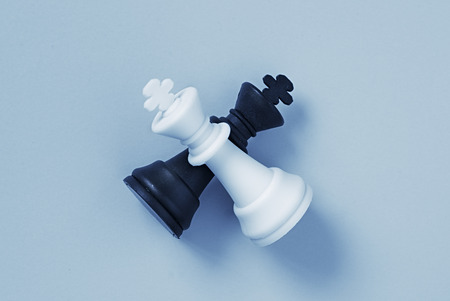 battle plan: Two chess kings lying on a light blue background with slight set shadow