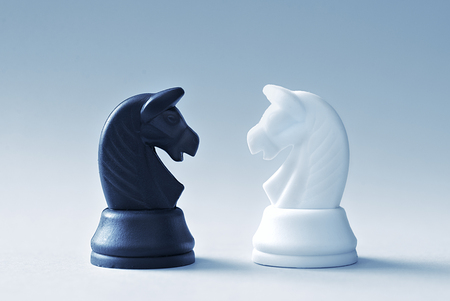 chessman: Confrontation of chess knights on a light blue background with slight set down shadow