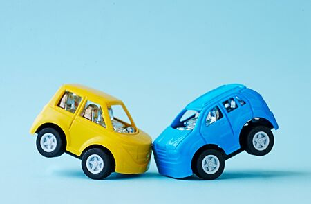 Close-up of a collision of two toy cars on a blue background Stock Photo