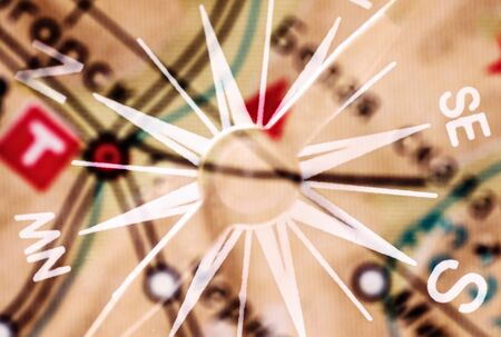 geographical: Detail of a magnetic compass on the background of the blurred image of the geographical map
