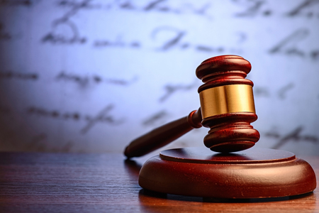 Wooden judge or auctioneers gavel on a plinth with a defocused background of a hadwritten document conceptual of justice and sentencing Stock Photo