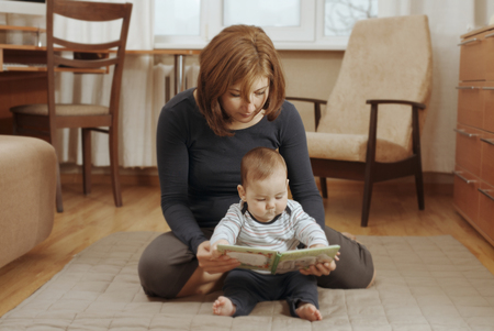 baby sit: Mother reading a book with her cute little baby boy as they sit together on the living room floor spending quality time together