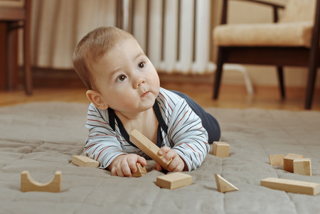 fascination: Adorable young baby boy playing with his toys lying on the carpet surrounded by wooden building blocks looking up to the side in fascination