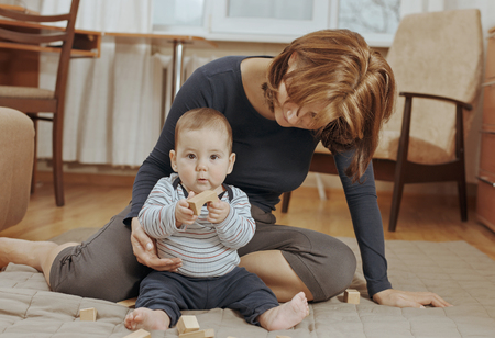 devoted: Cute small baby boy playing with educational wooden blocks in different shapes watched closely by his devoted young mother