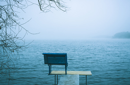 obscured: Lonely empty bench on the end of a jetty overlooking a cold bleak winter lake or sea obscured by mist or fog in a blue toned landscape