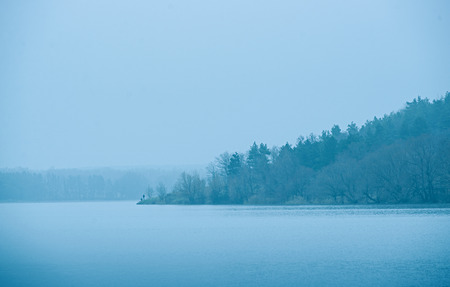 dismal: Cold blue toned lake in winter with leafless deciduous trees silhouetted against the mist on a promontory or island in a bleak weather or nature background