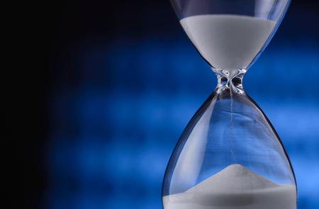 arena: Arena que se ejecuta a través de una medición de reloj de arena cuenta regresiva del tiempo hacia una fecha límite que pasa, vista de cerca de las ampollas de vidrio con y de la copia