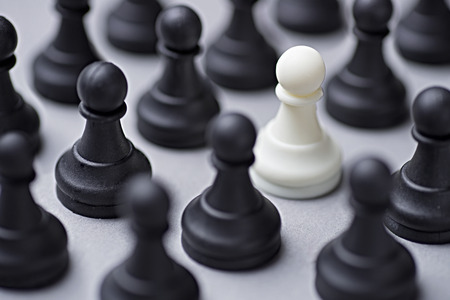 white colour: Single white chess pawn amongst black ones in a conceptual image with selective focus to the piece