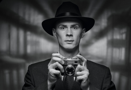 inscrutable: The detective takes on the camera. Black and white front view of business man in hat and suit holding vintage single lens reflex point and shoot camera