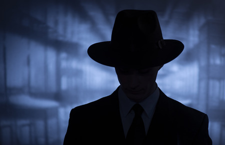 Silhouette of a mysterious man in a vintage style wide brimmed hat in a close up head and shoulders portrait