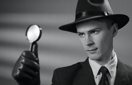 clues: Handsome young vintage detective wearing a hat holding a magnifying glass in his gloved hand as he searches for clues, black and white portrait