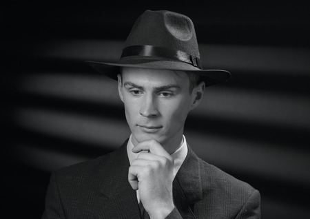 The detective thinks. Vintage black and white portrait of a thoughtful handsome young man in a stylish hat and suit with his hand to his chin staring pensively at the floor