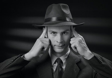 faraway: The detective thinks.Black and white front view close up on handsome 1950s style man touching his head with fingers