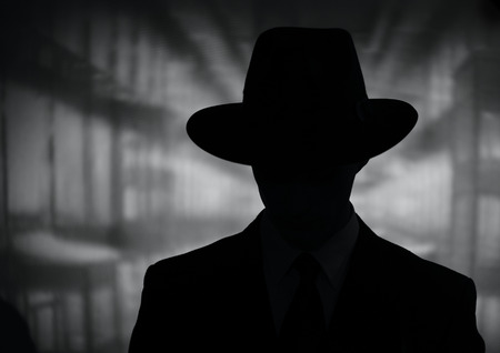 undercover agent: Silhouette of a mysterious man in a vintage style wide brimmed hat in a close up black and white head and shoulders portrait Stock Photo