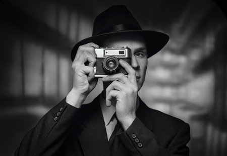hobbies: Single 1950s man in business suit and hat taking a picture over urban building background
