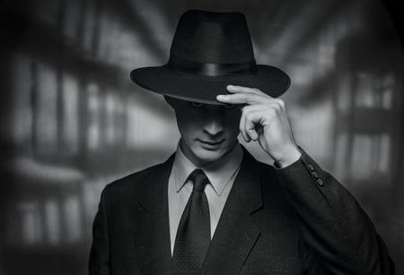 De rechercheur neemt de camera. Vintage stijl zwart-wit beeld van een beleefde jonge man in een pak doffing zijn hoed in erkenning of groet
