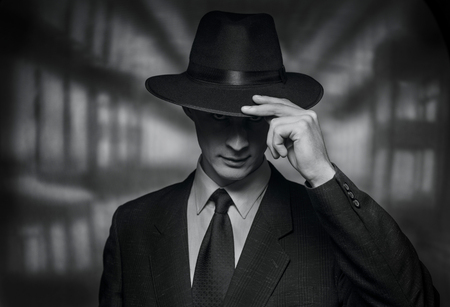 acknowledgement: The detective takes on the camera. Vintage style black and white image of a polite young man in a suit doffing his hat in acknowledgement or greeting