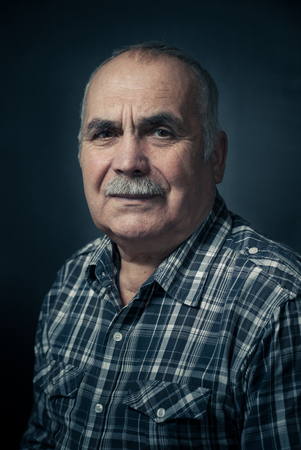 amiable: Portrait of serious mature man with mustache in check shirt Stock Photo