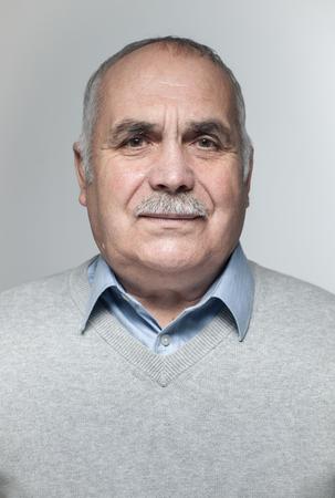 mature man: Portrait of balding mature man with mustache in sweater, studio background