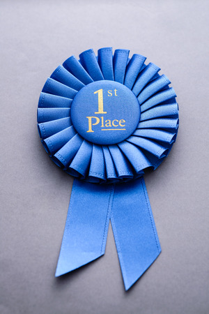 pleated: Blue pleated ribbon championship rosette for first place with gold text lying on grey in a concept of sport, competition and success