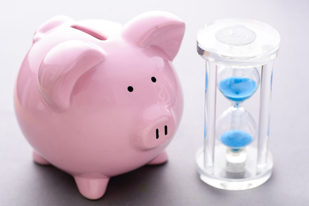 High-angle close-up view of cute piggy bank near classic hourglass with blue sand pouring