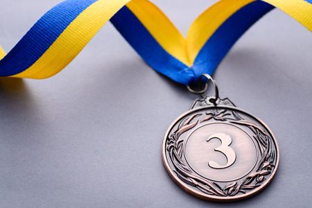 Close-up studio shot of third place bronze medal with striped blue and yellow ribbon on gray background