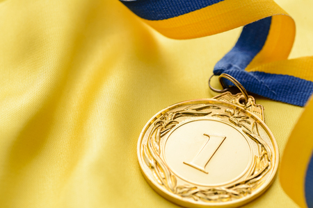 twirled: Champions first place gold medal on a twirled ribbon to be awarded to the winner of a competition or sporting event on gold cloth with copy space