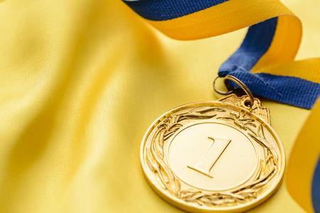 tissu or: Champions première médaille d'or de placer sur un ruban tournoyer à attribuer au gagnant d'une compétition ou manifestation sportive sur le tissu d'or avec copie espace