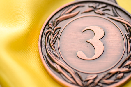Close up of an embossed third place bronze medallion lying on gold fabric with focus to the 3 in a concept of winning, achievement, success and competition Stock Photo