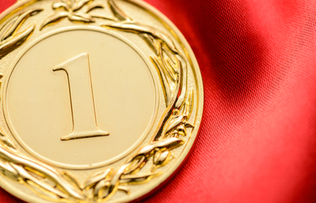 Embossed gold winners medallion for the first place in a competition or championship with a large number 1 in the centre on red fabric with copy space Stock Photo