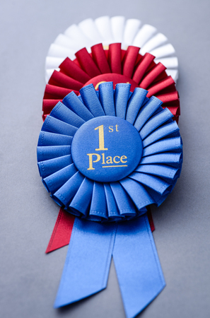 First, second and third placed red, blue and white winners rosettes stacked on a grey background in a sport and achievement concept