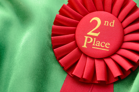 Colorful red winners 2nd place rosette to be awarded in a competition or sporting championship with pleated ribbon and gold text on a green textile background Stock Photo