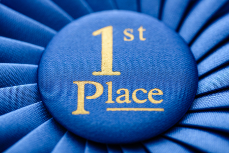 pleated: Winners blue first place rosette in soft textured fabric and pleated ribbon with a close up view on the central gold text Stock Photo