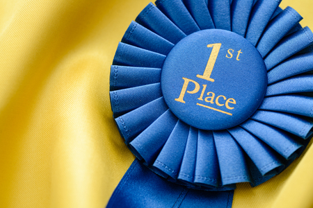 Blue Ist place winners rosette with pleated ribbon lying on gold fabric with copy space conceptual of succes, championship, competition, and achievement Stock Photo