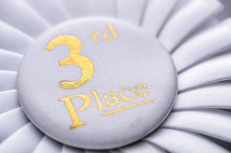 Third place winners white rosette with gold text and a pleated ribbon in a close up oblique angle view conceptual of competition and achievement