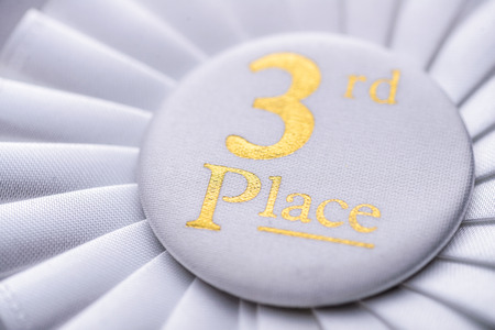 pleated: Third place winners white rosette with gold text and a pleated ribbon in a close up oblique angle view conceptual of competition and achievement