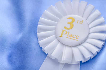 white achievement: Third place winners white rosette with gold text and a pleated ribbon in a close up oblique angle view conceptual of competition and achievement