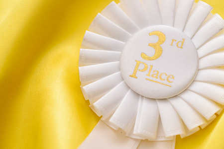 Close up view on a white ribbon rosette with gold text for 3rd place in a competition or sporting championship over a golden fabric background with copy space