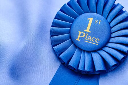 primer lugar: Winners blue first place rosette in soft textured fabric and pleated ribbon with a close up view on the central gold text Foto de archivo