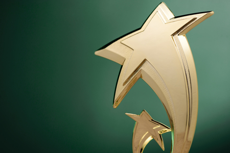 Low angle close up view of two stylish curving gold shooting stars over green with copy space