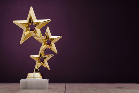 Gold winners award with three stars to be awarded to the first place in a competition or championship standing on a pedestal against a purple background with copy space 版權商用圖片 - 71046064
