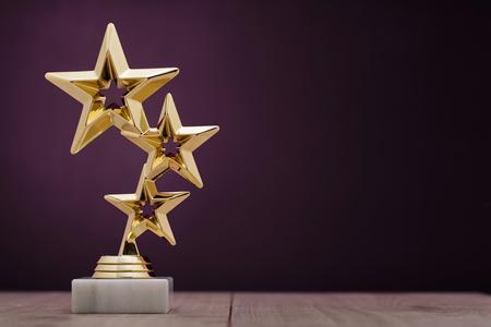 premios: premios ganadores del oro con tres estrellas que se otorgará al primer lugar en un concurso o de un campeonato que se coloca en un pedestal contra un fondo púrpura con el espacio de la copia