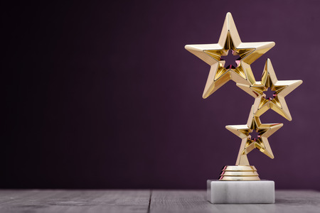 Gold winners award with three stars to be awarded to the first place in a competition or championship standing on a pedestal against a purple background with copy space